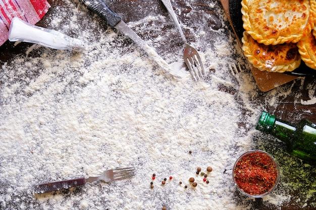 木製のテーブルの背景に小麦粉が振りかけられています。