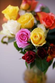 木製のテーブルの上に花の花束。透明なガラス花瓶のフラワーアレンジメント。