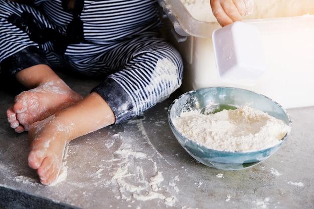 子供が遊んでキッチンテーブルの上で手を出します。子供の足は白い小麦粉で染色されています。