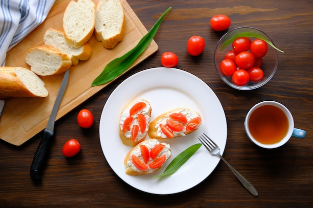 皿の上のパン、サンドイッチ、トマト、チーズのスライス。有機農産物。