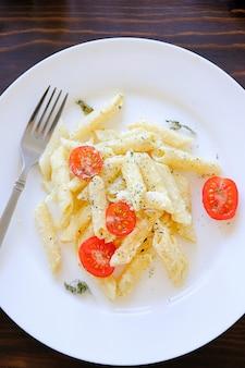 白い皿にクリームソースのパスタ。健康食品、菜食主義。