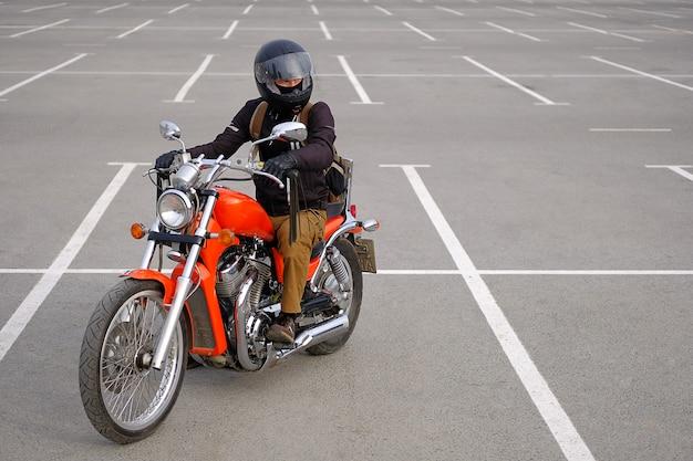 Байкер человек или парень-гонщик в защитном шлеме, сидя на мотоцикле.