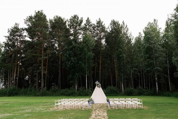 花と明るいサテンのリボンで飾られた白い木製の椅子、松の森での式典での結婚式の装飾