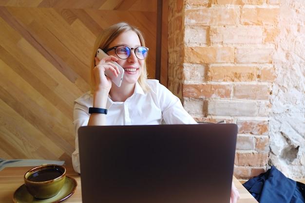 少女マネージャー、フリーランサー、笑みを浮かべて、携帯電話で話しているメガネの女性実業家。