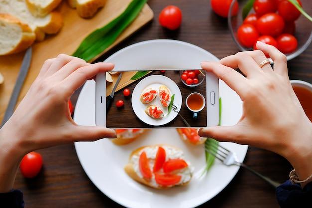 スマートフォンで朝食の写真を撮るブロガー