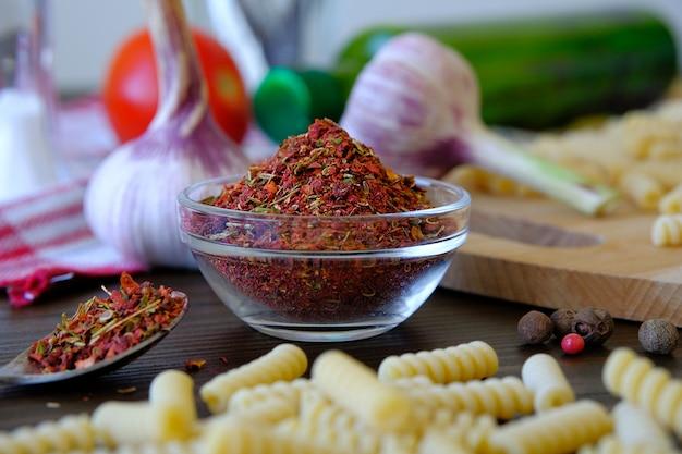 Сухие грузинские пряности или острая аджика для гурманов, в стеклянной чашке. рядом чеснок, красные помидоры, оливковое масло, макароны на деревянном столе.