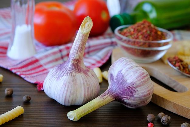 Чеснок, красные помидоры, сухие грузинские специи для гурманов, оливковое масло, макароны на деревянном столе.