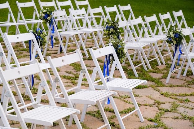 花で飾られた木製の椅子。式典での結婚式の装飾。