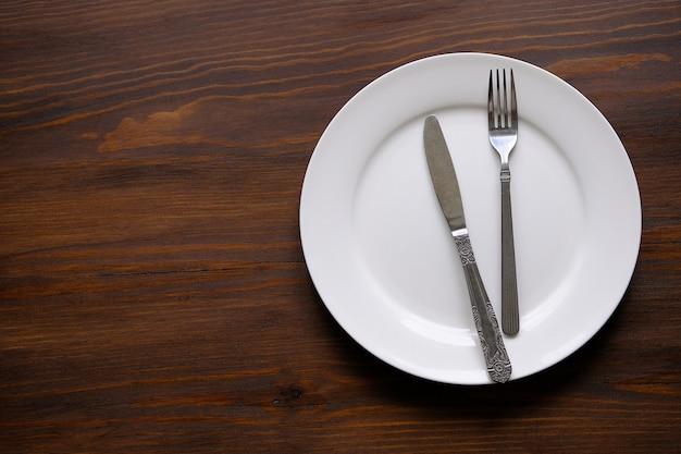 Столовые приборы на пустой белой тарелке.