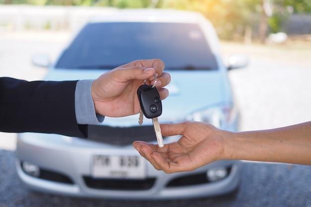 車のセールスマンは新しい車の所有者に鍵を送ります。中古車販売代理店、レンタカー