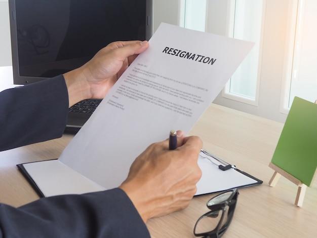 机の上に座っているエグゼクティブ。従業員辞任書を読む。