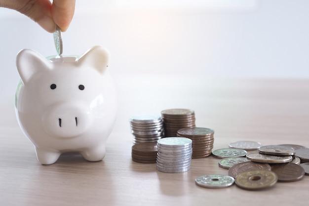 手が貯金箱にコインを入れています。お金の節約の概念