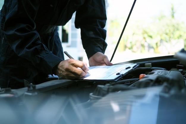 Инженер двигателя проверяет и ремонтирует автомобиль. выездные услуги по уходу