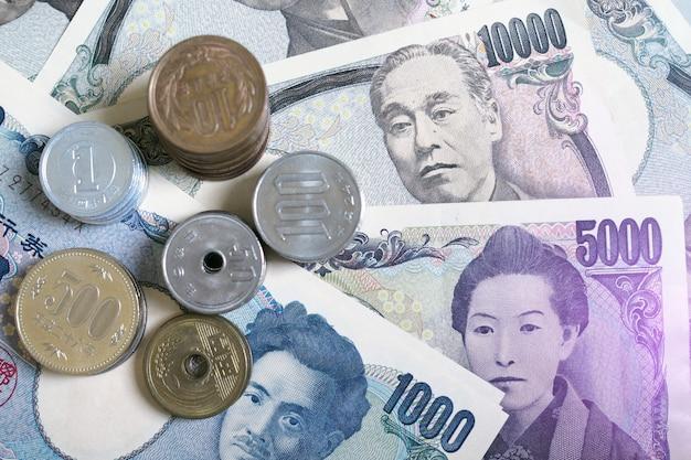 お金の概念の背景にある日本円ノートと日本円硬貨。写真は紫色の光です。