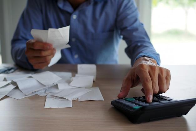 ビジネスマンは電卓を使用してテーブルに置かれた請求書を計算します。借金の概念