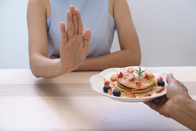 Женщины толкают кондитерские блюда. хватит есть десерт, крепкого здоровья