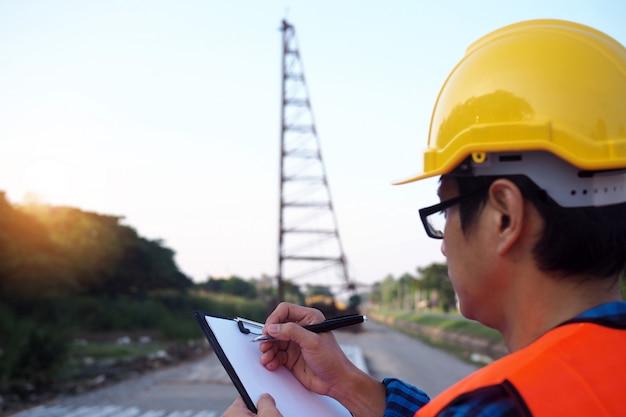 エンジニアはクリップボードを握り、建築区域の材料リストを点検します