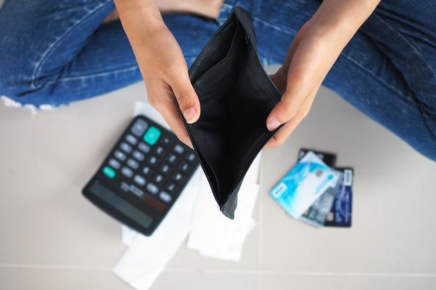 女性の手は空の財布を開きます。