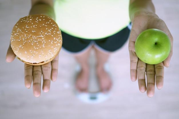 Женщины весят с весами, держат в руках яблоки и гамбургеры. решение выбрать вредную пищу, которая вредна для здоровья, и фрукты с высоким содержанием витамина с, полезны для организма. концепция диеты