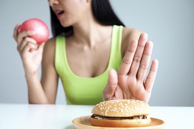 アジアの女性はハンバーガープレートを押して、健康のためにリンゴを食べることを選択します。