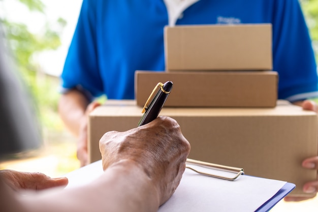 家主の手は、配達人から送られた小包を受け取るために署名しています。