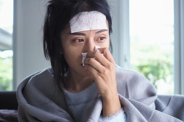 アジアの女性は、高熱と鼻水があります。病気の人の概念