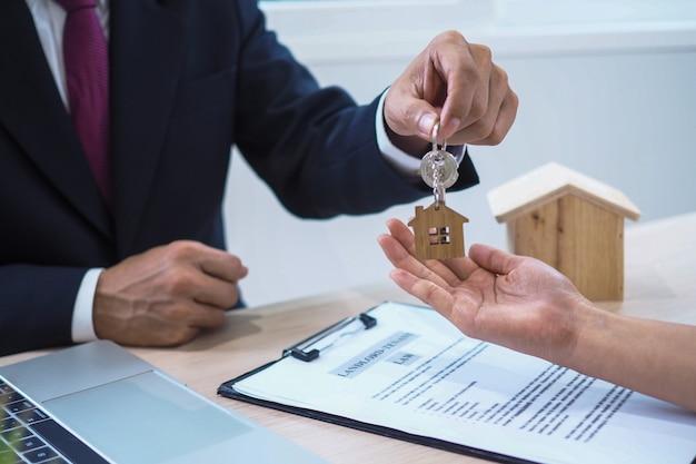 住宅購入者は販売者から家の鍵を受け取っています。家を売り、家を借りて、アイデアを買いましょう。