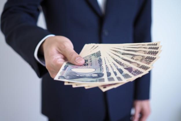 日本円紙幣を送るビジネスマン