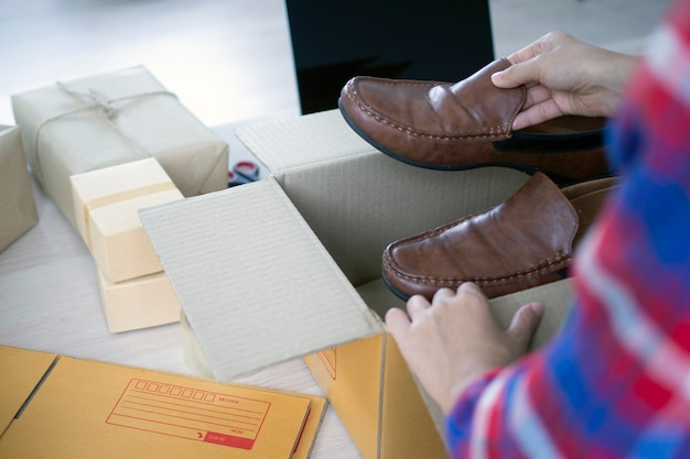 若いビジネス女性は、オンラインショッパーに商品を届けるための箱を準備しています。