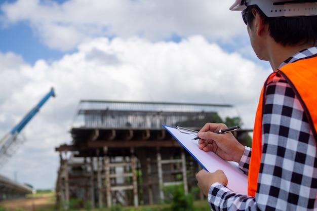 Инспекторы или инженеры проверяют работу группы подрядчиков по строительству моста через дорогу.