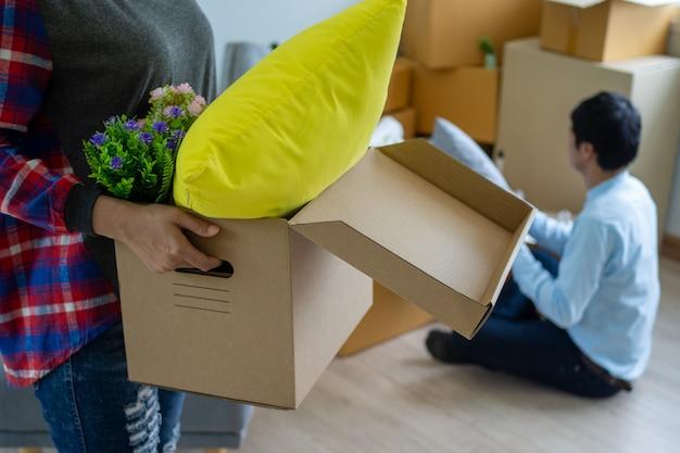 Жена несет коробку для личных вещей, а муж упаковывает коробку.