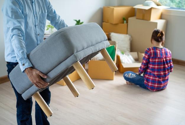 Муж несет мебель, а его жена упаковывает коробку