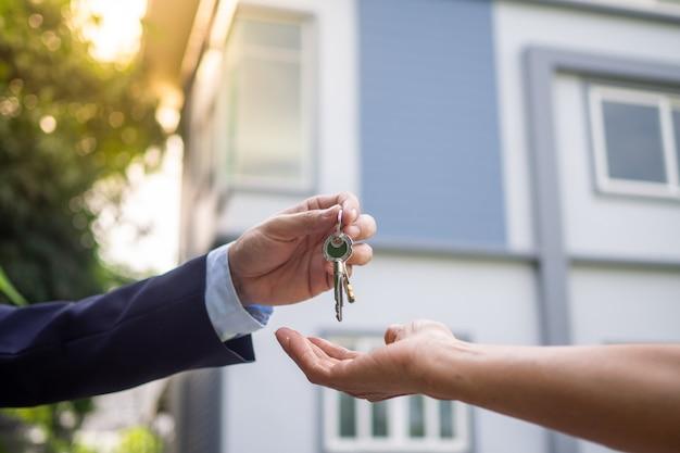Покупатели дома берут ключи от дома у продавцов. продайте свой дом, арендуйте дом и купите идеи.