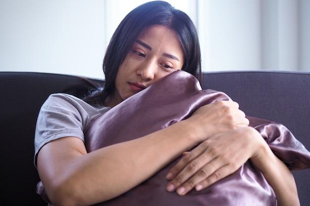 Азиатская женщина с душевной болью сидит в одиночестве, обнимая подушку.