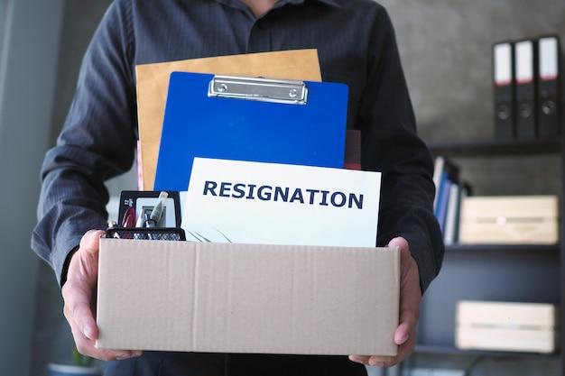 ビジネスマンは私物と辞任の手紙のための箱を握る