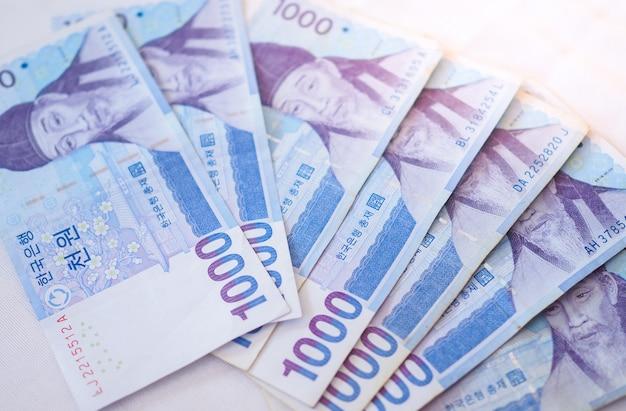 韓国人はお金の概念の背景のノートを獲得しました