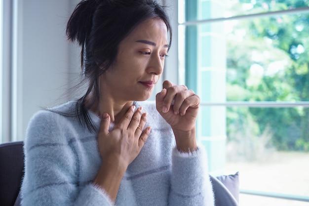 Азиатская женщина страдает стенокардией, высокой температурой и хроническим кашлем