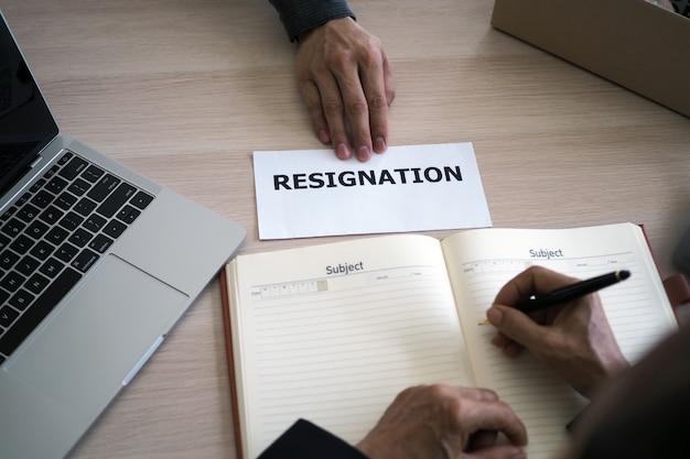 机の上の絵は経営者に辞任書を送るためにビジネス手を持っています