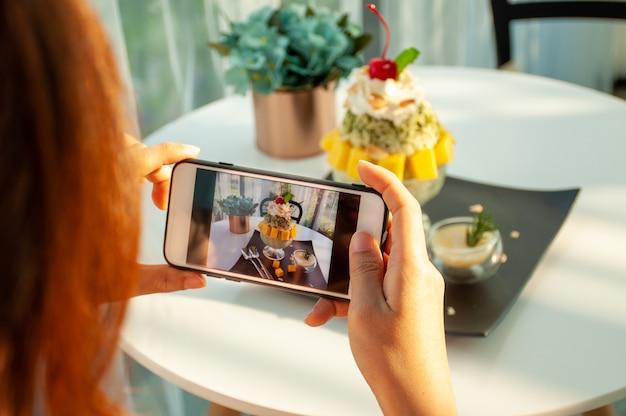 アジアの女性がカフェでマンゴーアイスクリームの写真を撮って、ソーシャルアプリにアップロードする準備をする