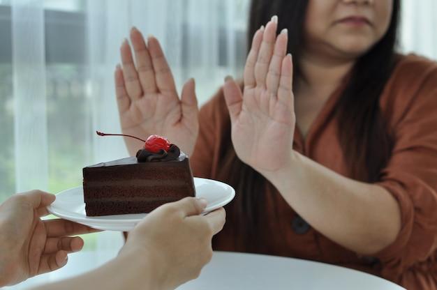 Женщина толкает тарелку с шоколадным тортом