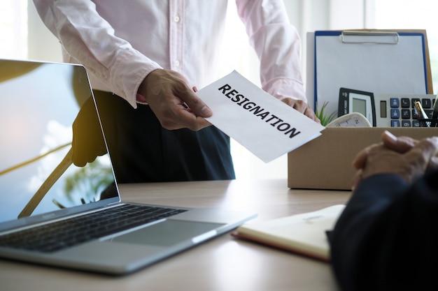 ビジネスマンは個人的な使用のための箱を持っており、幹部に辞任の手紙を送っています