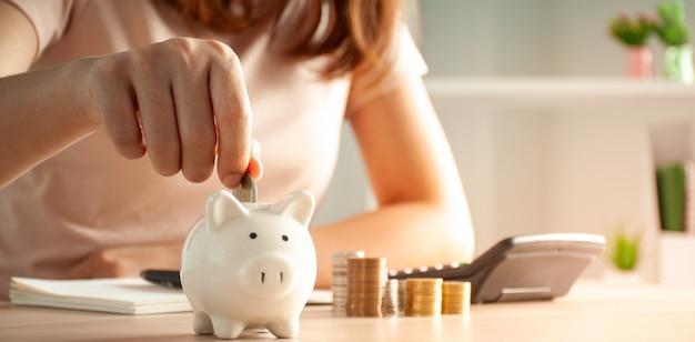 幸せなアジアの女性は貯金箱にお金を置きます