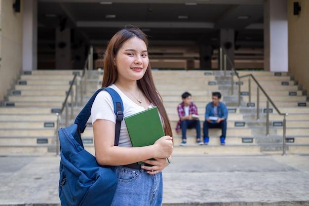 Ученик старшей школы держит книги в кампусе
