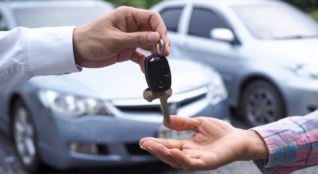 車のセールスマンは、新しい車の所有者にキーを送りました