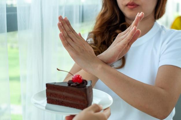美しい若い女性は、チョコレートケーキを拒否して、健康と形を大切にします。炭水化物と脂肪を含む食品を減らします。