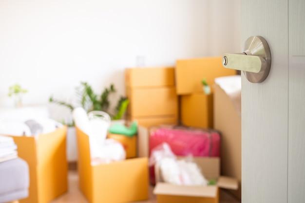 Дверь, которая открыта внутри комнаты, имеет личные вещи, ожидающие перемещения. переезд в новый дом
