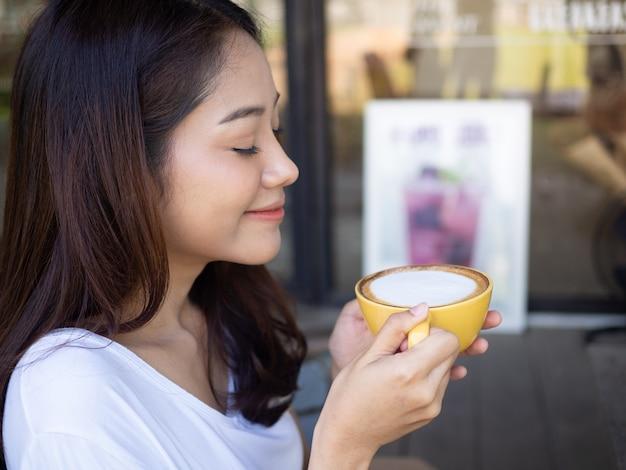 Милая девушка наслаждаясь выпивая кофе в свободном времени внутри кофейни с расслабленным жестом с улыбкой.