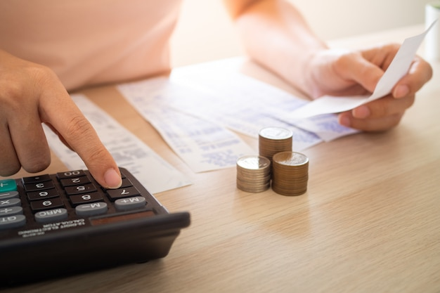 座って請求書を調べている女性は、計算機を押して、テーブル上の収入、支出、および支出の金額を計算します。自宅の居室内に。