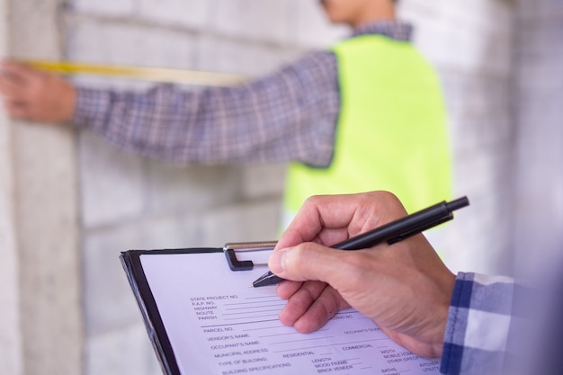 検査官は、プロパティが請負業者エンジニアと連携するように割り当てられている家のプロジェクトをチェックします。また、作業の詳細に注意して、パターンに合わせて準備を整えてください。
