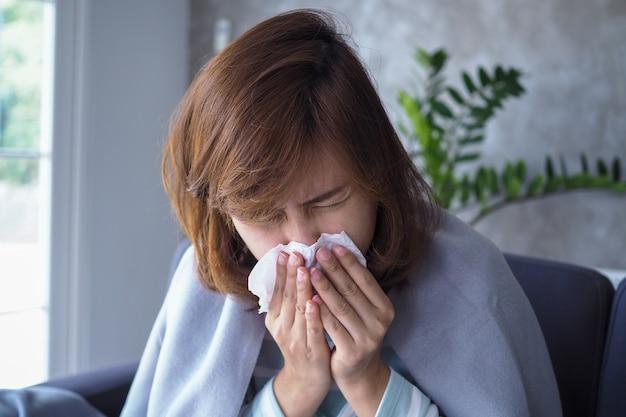 アジアの女性は鼻水があり、風邪をひき、咳、くしゃみ、発熱、家の中のソファーにうんざりしています。